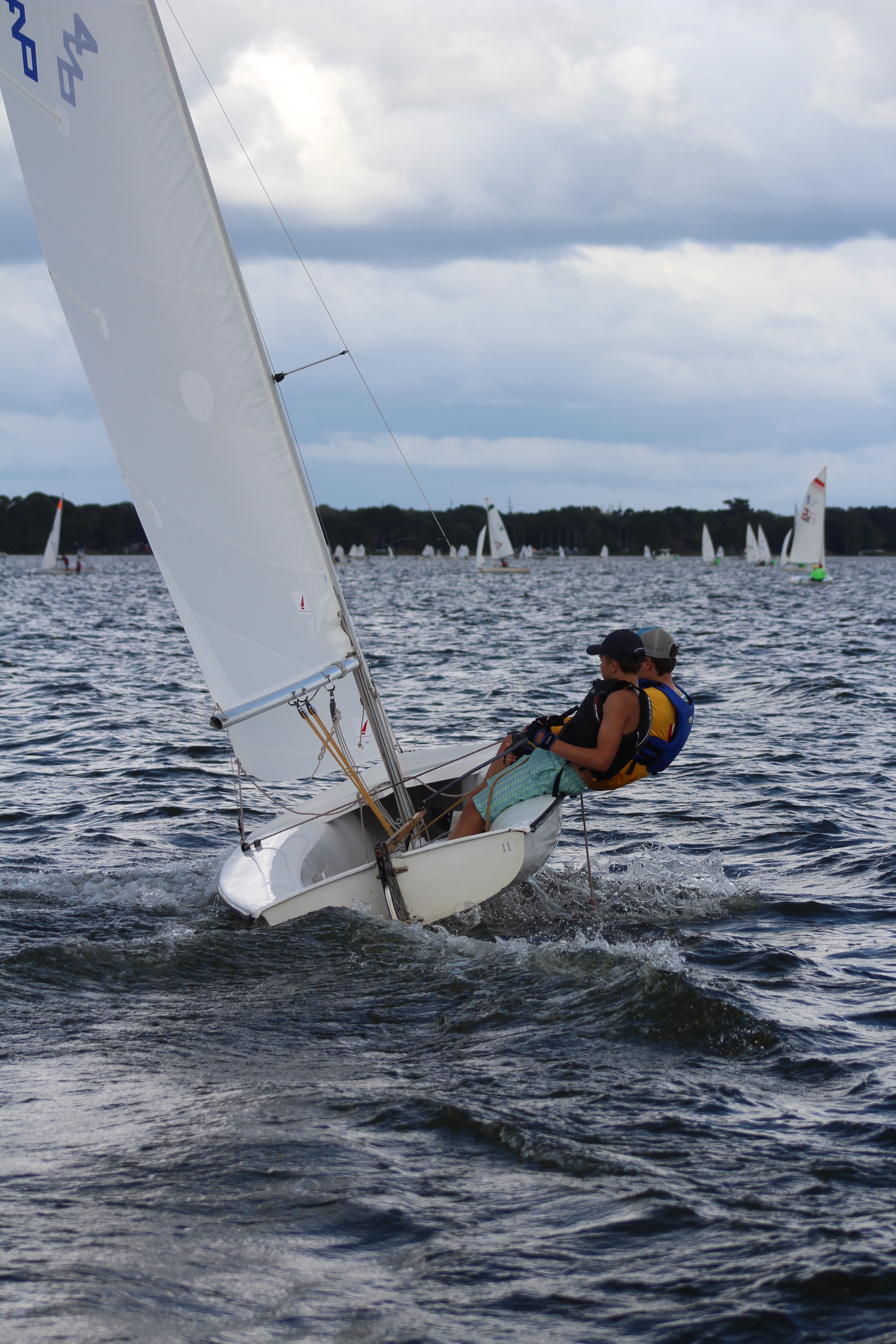 Two High School sailors on a 420, both leaning out to balance the boat.