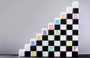 black and white blocks in a triangle shape with colored letters