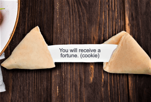 Open fortune cookie with printed saying on wooden table