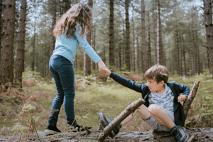 girl helping a boy stand up on a log