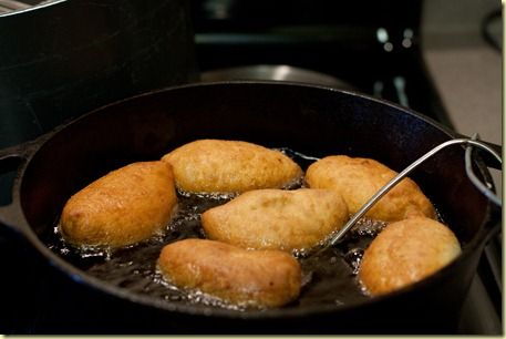 Meat piroshki being fried in a dutch oven.