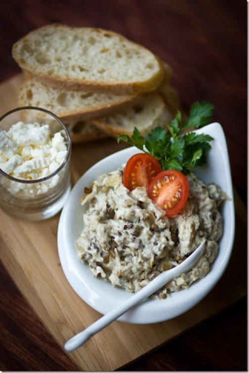 Eggplant spread topped with tomatoes and fresh greens in a white bowl and spoon on a wooden cutting board with a cup of cheese and sliced bread.