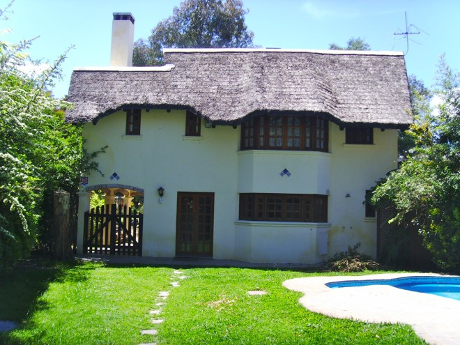 Image of backyard and white stucco home with thatched roof