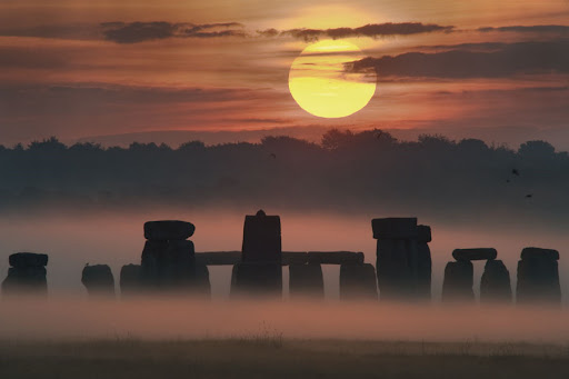 This image was taken during the week of the 2008 summer solstice at Stonehenge in United Kingdom, and captures a picturesque sunrise involving fog, trees, clouds, stones placed about 4,500 years ago, and a 5 billion year old large glowing orb.