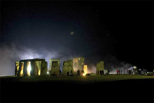 Stonehenge by night, with a single bright star in the sky and mist rising from the brightly floodlit stones. There are people around the stones, some in brightly coloured jackets.  To the right of the image is a large white van with people gathered around it and some unclear shapes which may be other vehicles.