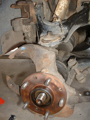 Then I took the brake caliper off and used a delicate and specialized tool called an old coat hanger to tie the caliper up and out of the way.  Then removed the rotor and then the tie rods using the same method as the last post.