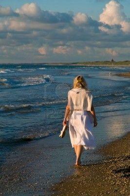 Mujer joven alejándose por la orilla del mar.