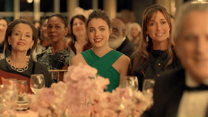 """Saat iklan ini dimulai Margaret duduk dalam sebuah acara penghargaan. Dia terlihat canggung dan tidak nyaman. Perhatikan kalung """"mata satu"""" yang dikenakan oleh wanita di sebelah kiri."""