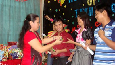 Ma'am Beth distributes prizes to parlor games winners.