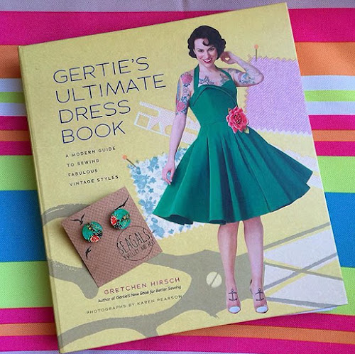 Gertie's ultimate dress book featuring woman with green rockabilly dress, plus green earrings.