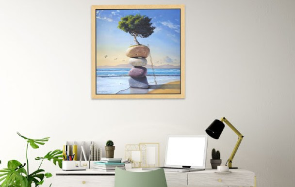 Paul Bond artwork hangs above desk with plant and lamp
