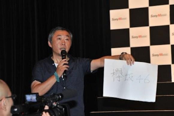 グループ名を鳥居坂46から欅坂46(けやきざか)に変更することを発表する今野氏
