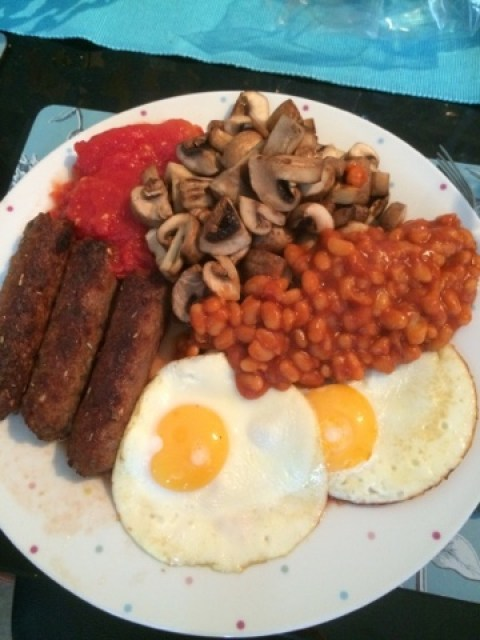 A plate with two fried eggs, 3 vegetarian sausages, fried mushrooms, tinned tomatoes and baked beans
