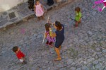 Nadia with a broom stick getting ready to hit her Piniata, while other kids are watching the preparations. The scene on a cobblestone street of Colonia San Rafael in San Miguel de Allende, Mexico.