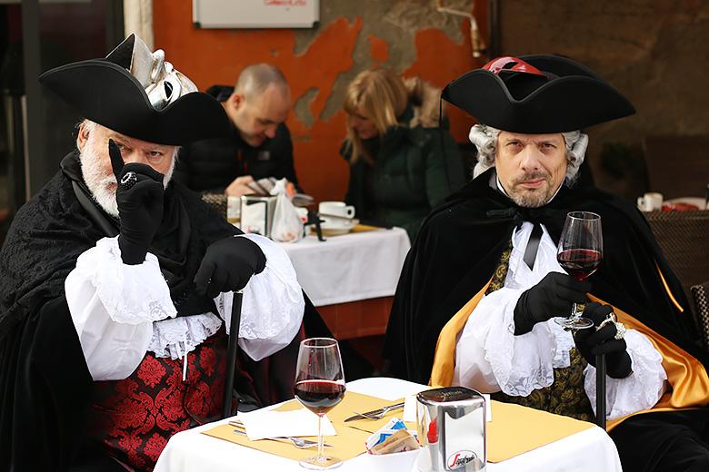 Hommes costumés à la terrasse d'un café vénitien.
