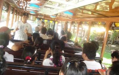 Sir Jojo interprets for deaf students inside the tranvia bus.