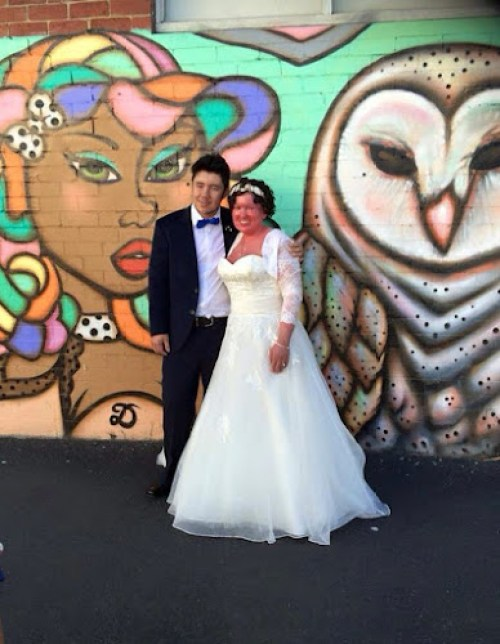 Adam and Carly a Findlay wedding photo - both in wedding attire, in front of street art