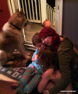 The girls comedown stairs, emma crying, for more hugs.