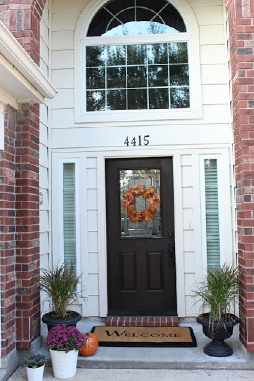 Glass front door Fall Porch Home Decor With purple mums, white pot and black flower pots Decorative pumpkins. Domesticability.com