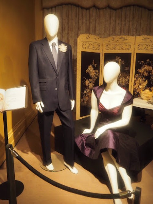 Liam Hemsworth and Kate Winslet's costumes from The Dressmaker - dark grey suit and plum coloured dress.