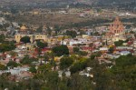 Panoramic view of San Miguel de Allende, Mexico from a small parking on road 111. Parroquia (parish church) towers to the right over the city. In the distance, there is a golf course and new developments.