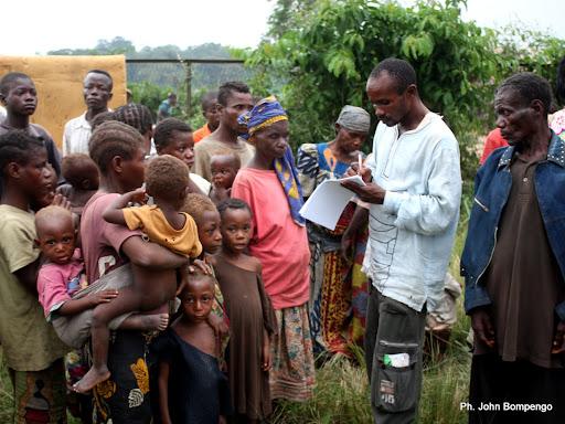 Carnet à mains, un préposé du HCR entrain d'enregistrer une famille de pygmées dans un centre des déplacés de Dongo(RDC) à Betou(RCA) le 18/11/2009. Ph. Don John Bompengo