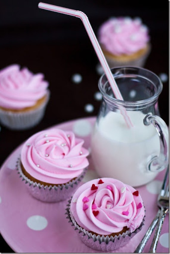 Two vanilla cupcakes on a pink plate with a pitcher of milk.