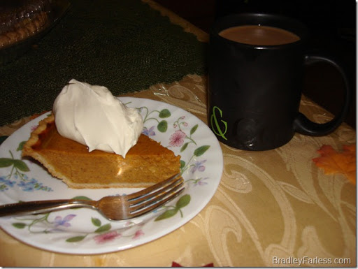Pumpkin pie with whipped cream and coffee.