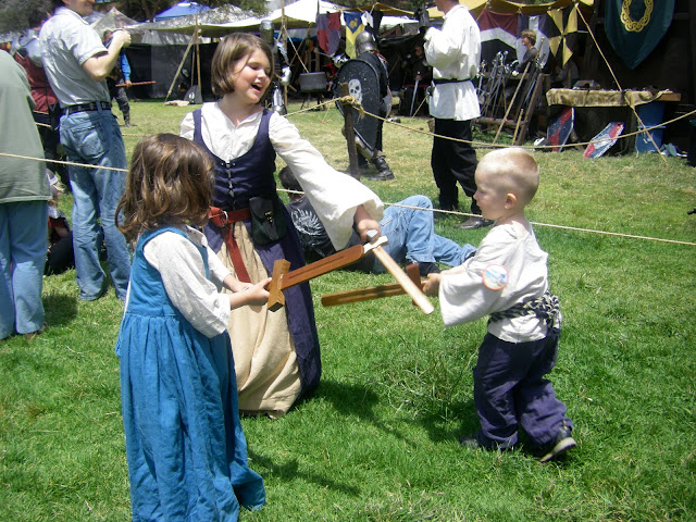 Taking on two older women in a battle of wooden swords.