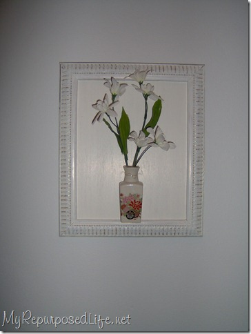 white thrift store frame holds a glass bottle