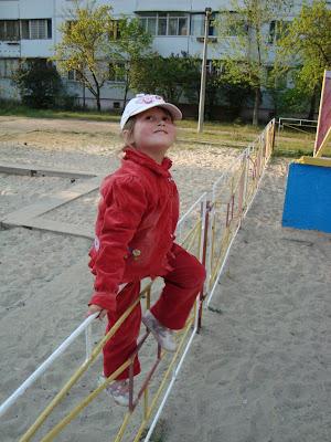 Кристина перелазит через забор и позирует на камеру