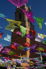 A church, adjecent to the Parroquia (parish church) near the main square (Jardin Allende) of San Miguel de Allende, Mexico viewed through paper cut-out decorations for the Day of the Dead (Dia de los Muertos).