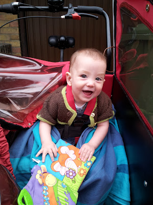 Baby sitting up on box seat of a cargo bike, smiling at the camera and playing with a book