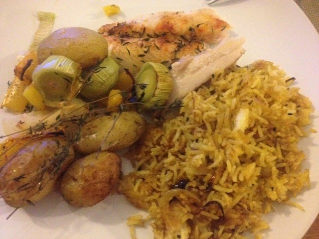 Baked fish with rosemary, potatoes and leeks, served with spicy rice