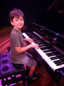 Boy sits at the piano