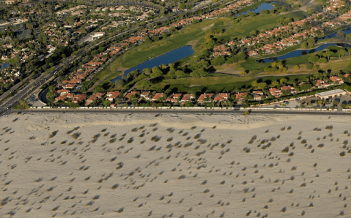 This 3 April 2015 aerial photo shows golf course communities bordering the desert in Cathedral City, California. In an aggressive push to reduce water usage statewide, California regulators are proposing that the biggest urban water users cut consumption by as much as 35 percent during 2015. Photo: Chris Carlson / AP Photo