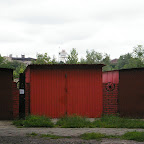 Lock-up garages painted red with an old shaft in the background.