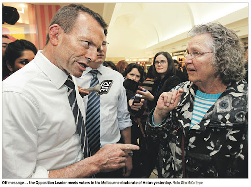 Tony Abbott is in the middle of a shopping centre, surrounded by minders and journalists - he is jabbing his index finger towards an elderly woman with his eyes squinted, his chin down and his lip curling - the woman is taken aback, her eyes wide and staring