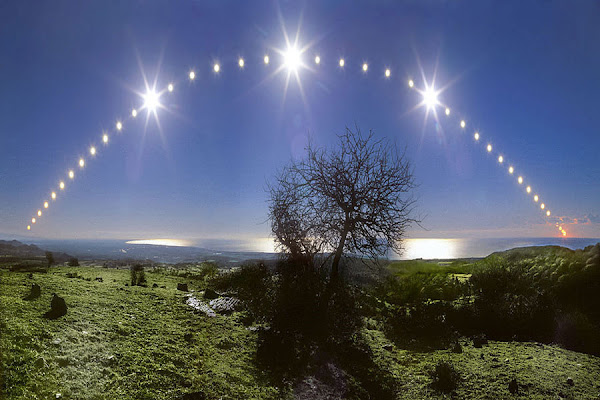 This striking composite image follows the Sun's path through the December solstice day of 2005 in a beautiful blue sky, looking down the Tyrrhenian Sea coast from Santa Severa toward Fiumicino, Italy. The view covers about 115 degrees in 43 separate, well-planned exposures from sunrise to sunset.