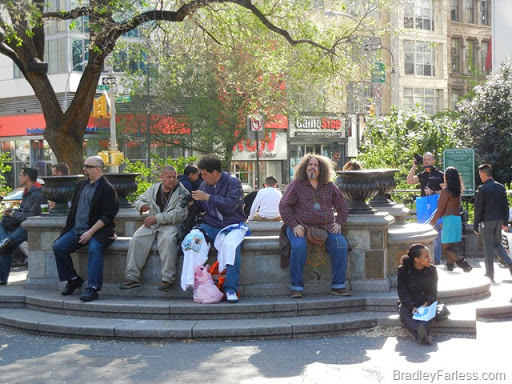 People sitting on a fountain in Union Square.