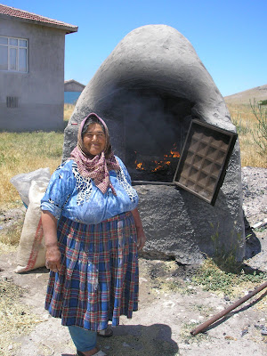 A Turkish woman makes some bread with a rad mud oven.