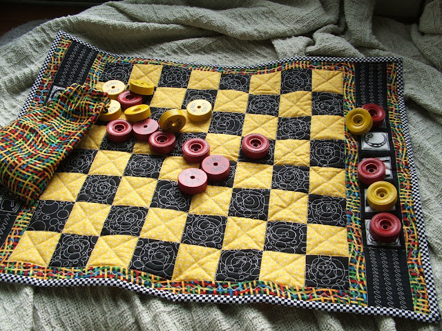 A checker quilt for Liz.  It was pieced with her name on it and included coordinating checkers and storage bag