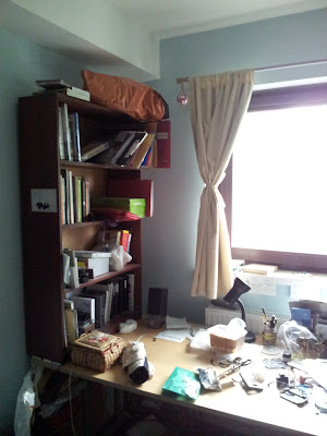 Shot of left-hand side of desk, with dark wood bookcase standing on it against the wall)