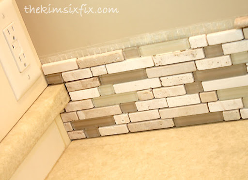 vanity with a custom tile backsplash