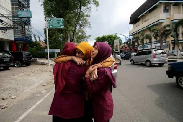 Mulheres se abraçam em Banda Aceh logo após a notícia do terremoto e do alerta de tsunami nesta quarta-feira (11) (Foto: AFP)