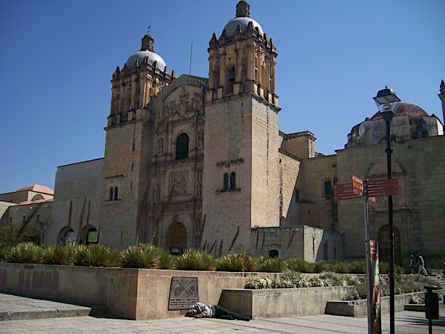 La placa de Patrimonio Cultural de la Humanidad, en el fondo la Ibglesia de Sto Domingo, y una CRUDA realidad
