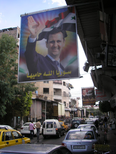 This is the president of Syria. You might think, by looking at him, that hes a massive chump. You might notice, for example, his jowls which he has failed to conceal by craning his neck; his neck which is freakishly long and which he has accidentally accentuated while trying to conceal his jowls; his tiny little moustache; the other picture of him in the background; HIS HALO; the fact that he looks like someone who didnt get into the police or any number of other features. You might also know that these photos and others with even more messianic imagery are plastered all over Syria, and yes, it does all point to chumpery. But did you know that he never wanted to be president? His older brother was going to inherit the title from their father (in the standard democratic tradition) but accidentally died in a car accident. Bashar was going to be an opthalmologist but was thrust unwillingly into politics. So who can blame him for making a few concessions to chumpery?