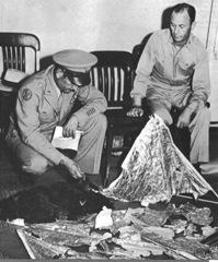 Militares mostrando os pedaços do então balão meteorológico que havia caído em Roswell.