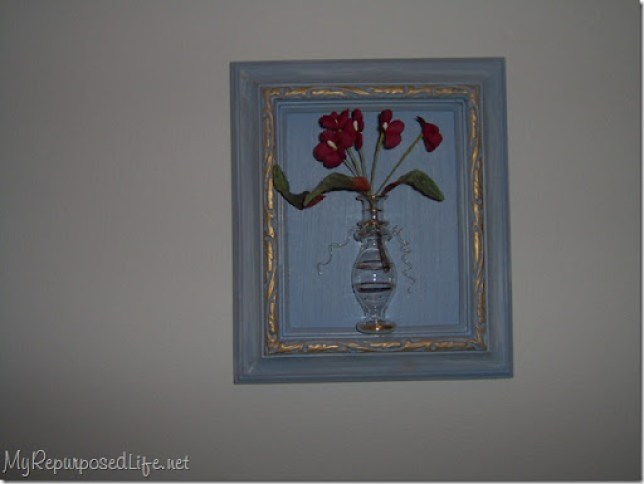 blue frame with gold highlights holding a vintage glass bottle