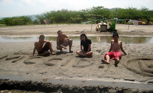 Deaf students and Sir Jeff sitting on a beach with MCCID shaped in sand